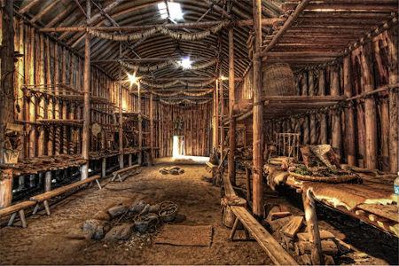 """L'interno di una """"Longhouse"""" o Casa Lunga Irochese. Simbolismo e pragmatismo della Gayanashagowa nascono da questa struttura, che rappresenta il cuore della millenaria esperienza dei Clan Irochesi"""